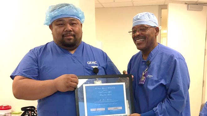 Surgical technician Brian Fegurgur, left, receives the Guam Regional Medical City CEO Award from Lester Whitley, manager of perioperative services, Monday, Jan. 23, 2017.