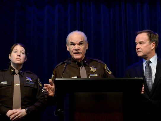 Ingham County Sheriff Gene Wriggelsworth, flanked by