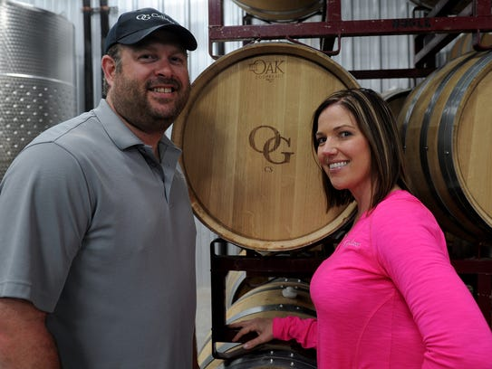 James and Sammi Hanger pose in front of a cask of wine