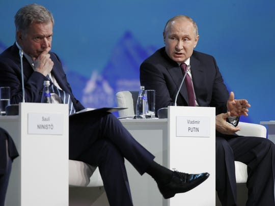 Russian President Vladimir Putin, right, gestures while speaking as Finnish President Sauli Niinisto listensat a plenary session of the International Arctic Forum in St. Petersburg, Russia, Tuesday, April 9, 2019.