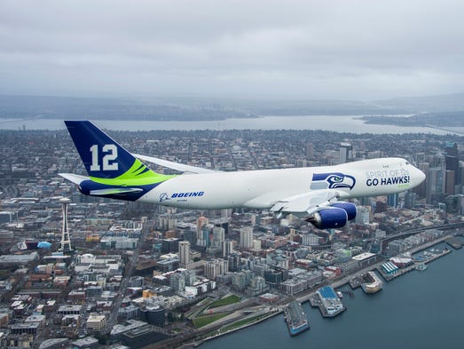 An aerial shot of Boeing's Seattle Seahawks-themed 747-8F freighter flying within view of the downtown Seattle skyline.