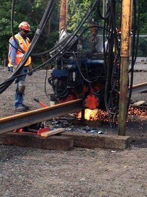 Putting the rail in M-1 Rail: Construction crews welding, grinding, and polishing sections of steel track prior to laying them along Woodward Avenue for the street project. M-1 Rail is expected to be ready to carry passengers by late 2016.