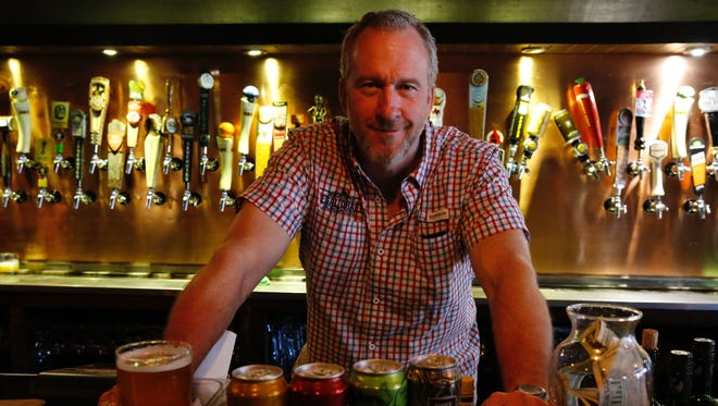 Greg McCarthy, co-founder of Legal Draft Brewery, stands over some of his company's beer.