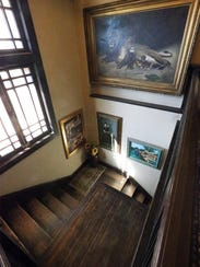 Art pieces decorate the wooden staircase in the Henry