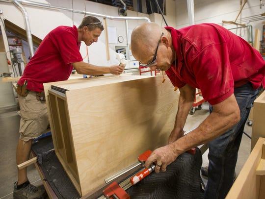 Eric Linssen (left) and Mark Strothman work on a pedastal