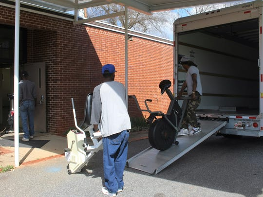 Workers haul fitness equipment out of the Jim Ed Rice Center in Anderson on Thursday.