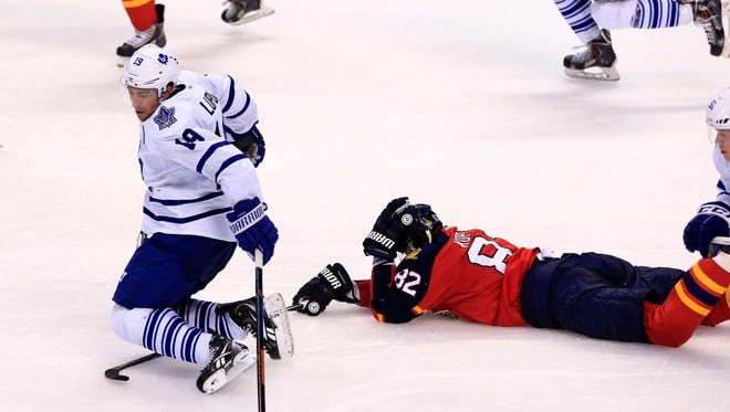 Toronto Maple Leafs right wing Joffrey Lupul (19) reaches for the puck after a collision with Florida Panthers left wing Tomas Kopecky (82) in the second period at BB&T Center.