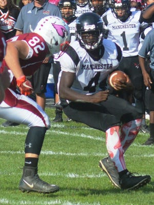 Manchester running back Osman Kanu (4) trying to get by Pompton Lakes defender Philip Latora.