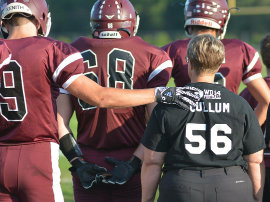 Wes-Del player Kyle Dosch puts his arm around Amy Cullum during a ceremony to honor Alex Cullum.