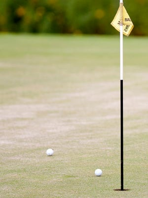 Two golf balls rest near the pin on the third hole during Wednesday's high school golf match at Links at Lang Farm in Essex.