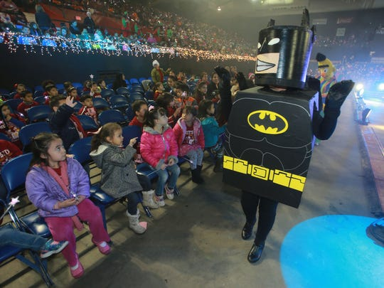 A Batman figure waves to Westside Head Start Center students at the El Paso County Coliseum.