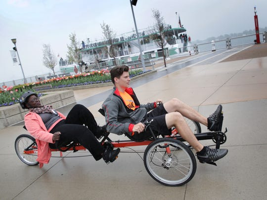 Georgea Cole, left and Jared Long ride a recumbent tandem on the Detroit riverfront on Tuesday, May 15, 2018. MoGo launched its bike share program a year ago and is now starting an Adaptive MoGo bike share program that will be available at Wheelhouse Detroit in Rivard Plaza.