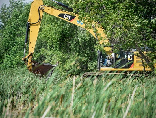 An excavator removes floating bogs Wednesday, July