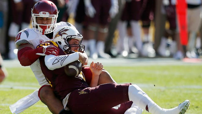 Washington State's Daniel Ekuale, sacks Arizona State quarterback Taylor Kelly during the first half on Saturday, Nov. 22, 2014, in Tempe.