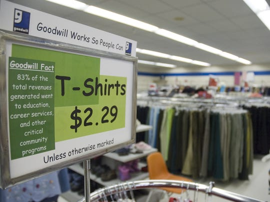 A sign at the Indianola Goodwill store describes where some of the profits go as well as setting the price of T-shirts.