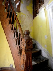 Sharon Burton walks down the ornate, curved staircase in the front of a house on Cherry Street in Lansing Thursday while she tours the place during an open house.