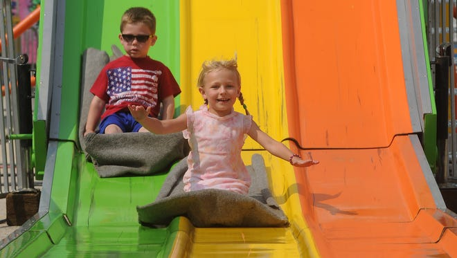 Carson Marchant, 4, of Oshkosh and Trinity Bartlett, 5 of Fond du Lac get some speed as they go down the Super Slide at the Fond du lac County Fair on Thursday.