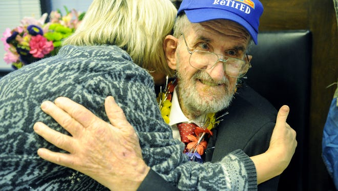 Pam Jeffries, owner of QP's Carry out, gives her friend, Bobby Ellis, a hug at Ellis' retirement party at the Courier & Press in 2012. Ellis, who delivered and sold Evansville's newspapers for more than 50 years, died on Monday.