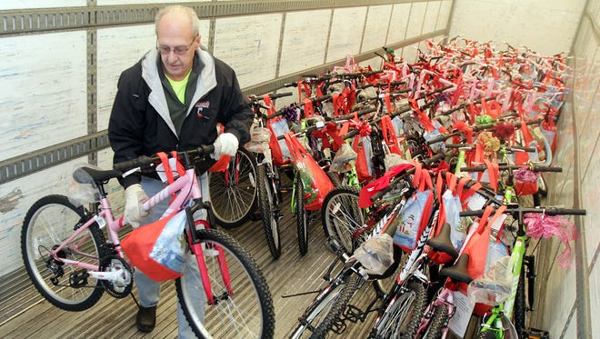 Mike Weil, a truck driver for Kroger Co., unloads one of the 116 bicycles donated to Hamilton County Job & Family Services by Bike Lady Inc., a nonprofit founded in 2008. The bikes were delivered to a warehouse in the West End and will be distributed to foster children over the next few weeks.