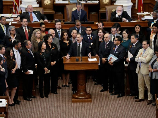 """Texas Rep. Rafael Anchia, D-Dallas, at podium, is surrounded by fellow lawmakers as he speaks against an anti-""""sanctuary cities"""" bill that has already cleared the Texas Senate and seeks to jail sheriffs and other officials who refuse to help enforce federal immigration law, Wednesday, April 26, 2017, in Austin, Texas. (AP Photo/Eric Gay)"""