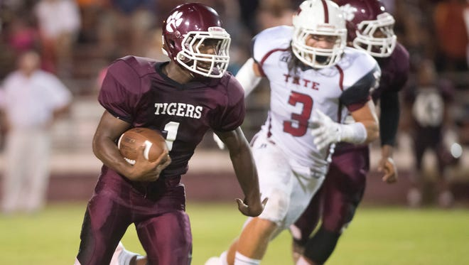 Pensacola High School's Kevon Abrams, (No. 1), left, turns up field for extra yards with Tate High School's Dallas Ditto, (No. 3) in pursuit.