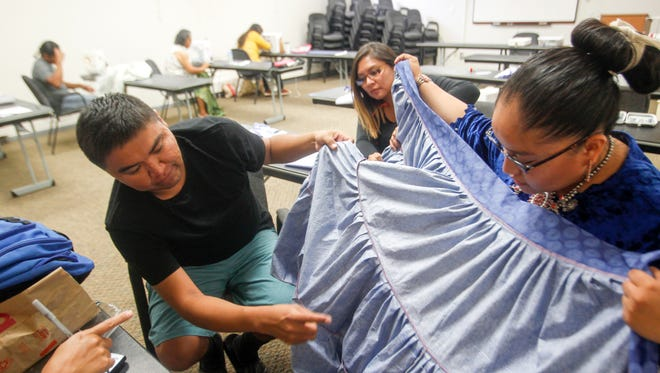 From left, workshop instructor Wilfred Jumbo and Sheryl Benally, administrator for the Navajo Cultural Arts Program, look over Miss Navajo Nation Crystal Littleben's skirt Sunday at Diné College's north campus in Shiprock.