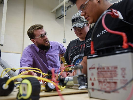Industrial technology teacher Adam Johnson works with