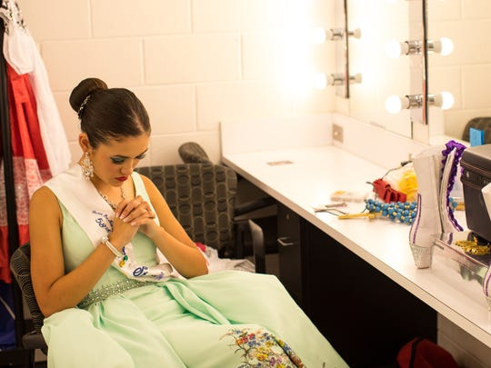 Contestant number 8 Victoria Morin says a prayer in the dressing room before the 58th annual Feria de las Flores in the Richardson Performance Hall at Del Mar College on Saturday, July 29, 2017.