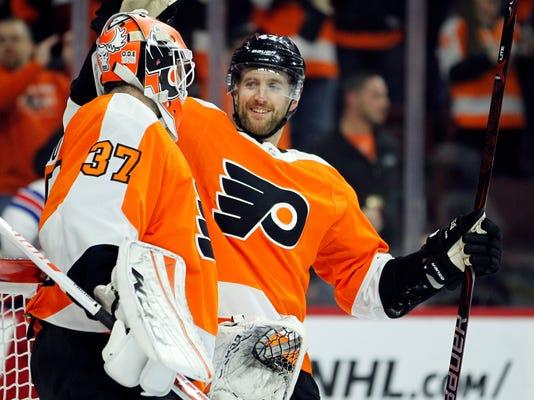 Philadelphia Flyers' Andrew MacDonald, right, congratulates goalie Brian Elliott at the end of an NHL hockey game against the New York Rangers, Saturday, April 7, 2018 in Philadelphia. The Flyers won 5-0. (AP Photo/Tom Mihalek)