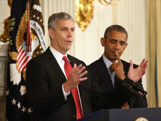 President Obama listens as Education Secretary Arne