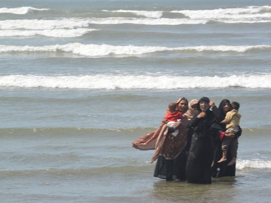 Pakistani women wade with their children in the Arabian