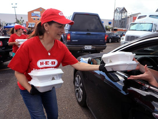 H-E-B employee Michelle Aquas distributes meals to