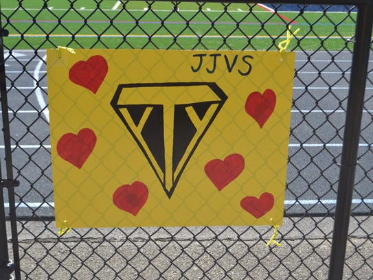 """A sign dedicated to """"Super Ty"""" hung on the fence around"""