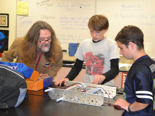 From left, Oakland Bay Junior High teacher Eric Stokely explains a tool to robotics team members Seth Lowe, 14, and Dylan Sedillo, both eighth-grade students at Oakland Bay Junior High. Stokely joined the staff this year and recently won a national award for his mentorship in the FIRST Robotics national competition.