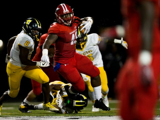 Immokalee's Abraham Alce (49) spins out of a tackle