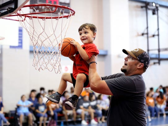 Cash Williams, 3, goes up for a dunk with an assist