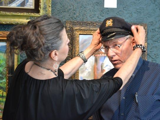 Rose Lucas Haninger adjusts a captain's hat – one of