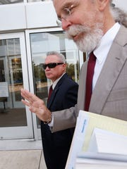 Mark Longoria, the 53-year-old CEO of Houston-based Drug Testing Corp., left, and his attorney Tom Fortner, leave the federal courthouse in Jackson, Miss., Wednesday, Aug. 3, 2016, after pleading guilty Wednesday to a felony count of conspiracy as part of a prison bribery scheme centering on former Mississippi Corrections Commissioner Christopher Epps.