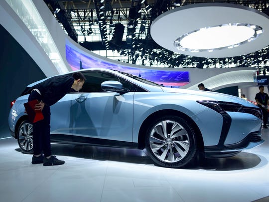 A man looks at a Buick Velite 6 car at the Beijing