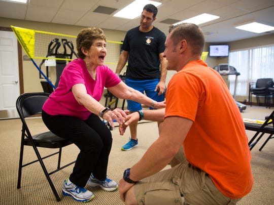 Beverly Lipson, 86, works on standing up and sitting down in a chair with her trainers, James Metcalf and Nino Magaddino, on Friday, July 21, 2017, at the Bradford Square retirement community in North Naples.
