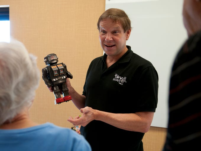 """Toy Scout"" Joel Magee appraises Horikawa's Super Astronaut toy robot for Jean and dick Saunders during the Indianapolis Vintage Toy Buying Show at the Airport Courtyard Marriott, Saturday, Aug. 9, 2014."