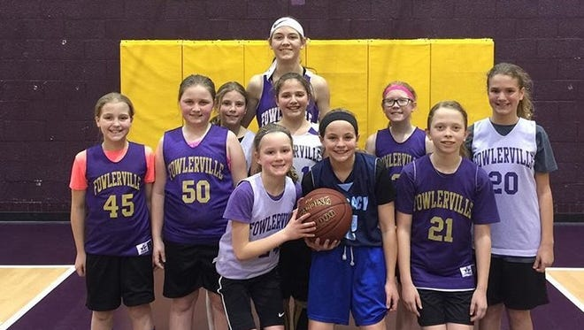 """Fowlerville varsity girls basketball player Elie Smith (back center) stands with a 6th Grade Red Cedar Team she helps coach. She said the group of  girls look up to the current varsity group as """"superstars."""""""