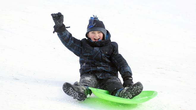 Caiden Delor, 10, of St. Clair, can't help but smile as he slides down the sledding hill at Columbus County Park.