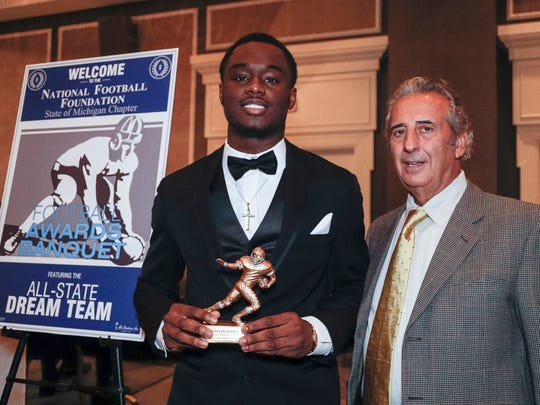 Detroit Free Press 2017 All-State Dream Team member Ovie Oghoufo of Farmington Hills Harrison poses for a photo with N.F.F. State of Michigan Chapter president Tony Versaci during the National Football Foundation State of Michigan Chapter awards banquet at the Dearborn Inn in Dearborn on Dec. 10, 2017.