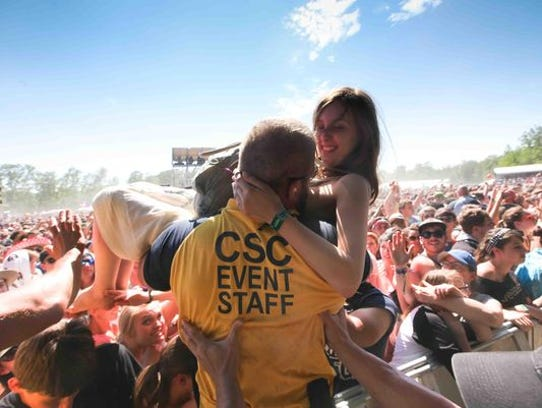 A fan is pulled from the crowd after surfing Sunday