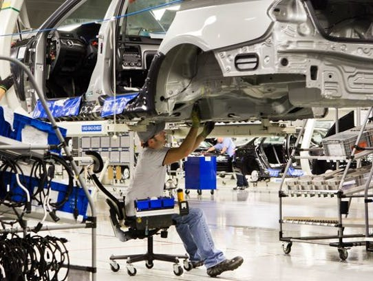 An employee works on a Passat sedan at the Volkswagen