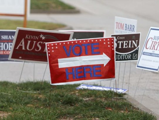 Campaign signs sit behind another showing voters to