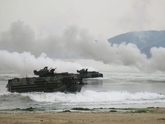 Marines aboard amphibious assault vehicles rehearse