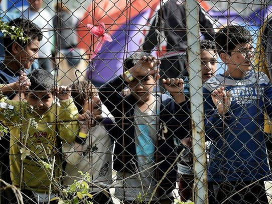 Children stand behind a fence inside the Moria migrant