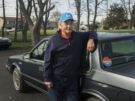Gettysburg resident Mike Lawn stands next to the car